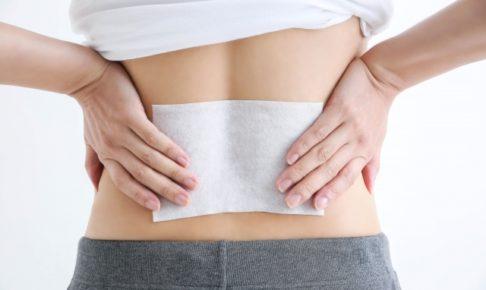 腰痛で湿布する女性